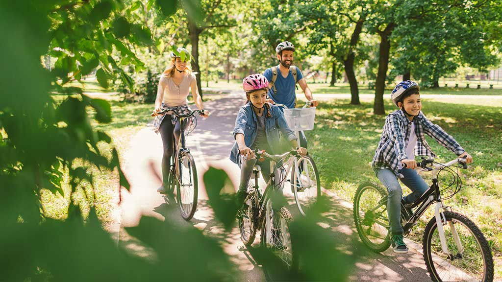 A family riding their bikes on a bike path surrounded by trees